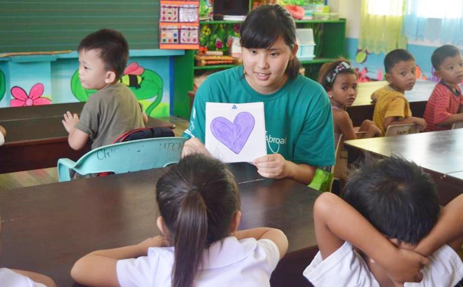 フィリピンの子供たちに英語で形の言い方を教える日本人高校生ボランティア